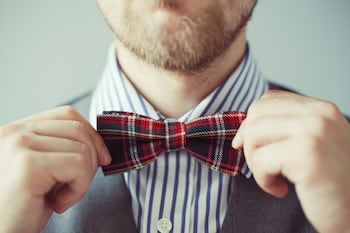 Close-up photo of a man with bard correcting his bow-tie