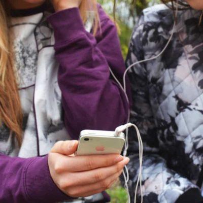 BFFs sharing headphones