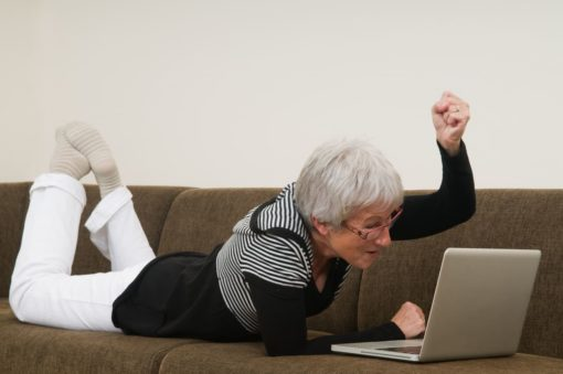 Woman on couch with laptop being excited