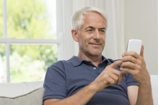 White haired man texting
