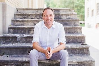 Joe Sanok seated on stairs outside