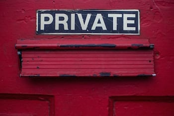"A red door with a letter slot in it, with the word ""Private"" written above the slot"