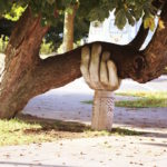 Sculpture of a large hand holding up a large tree limb