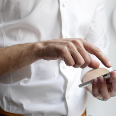 Man tapping screen of smartphone