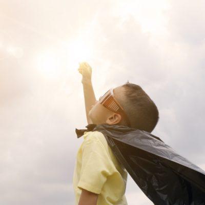 kid superhero wearing a cape
