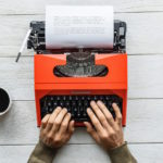 Hands typing on an orange typewrite