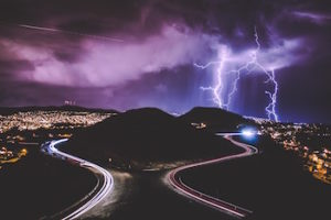 Dark sky with lightning strikes over twin hills with timelapse of cars on an interstate