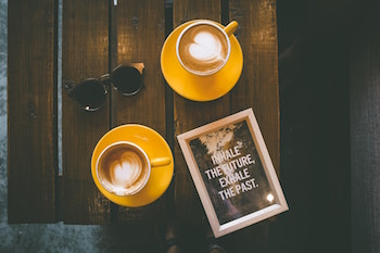"Latte art and a sign that reads, ""Inhale the future and exhale the past"""