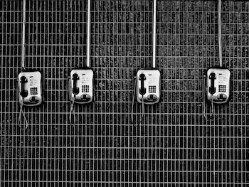 Black and white image of several old pay phones in a row on a wall