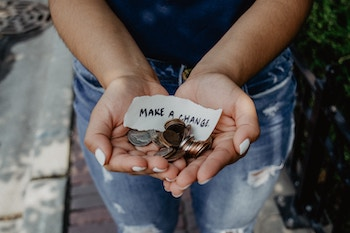 """Someone's hands holding coins and a sheet of paper saying, """"Make a change"""""""