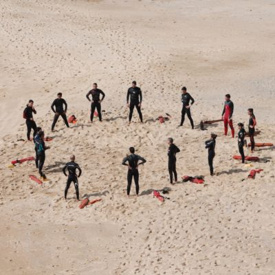 Lifeguards meeting in a circle on the sand
