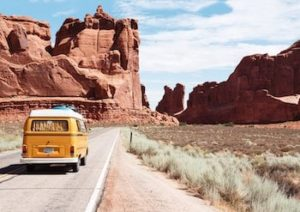 Vanagon driving down road towards desert rocks