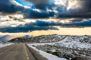 A hilly, rural road with storm clouds and snow on the ground